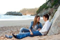Молодые красивые пары сидя на пляже. Стоковые Фотографии RF