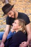 Молодые красивые пары сидя на следах поезда Стоковые Изображения