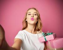 Молодые красивые подарки подарка на рождество владением женщины усмехаясь и сделать фото selfie с ее чернью мобильного телефона стоковые изображения rf