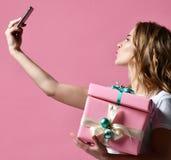 Молодые красивые подарки подарка на рождество владением женщины усмехаясь и сделать фото selfie с ее чернью мобильного телефона стоковое фото rf