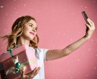 Молодые красивые подарки подарков на рождество владением женщины усмехаясь и сделать фото selfie с ее чернью мобильного телефона стоковая фотография rf