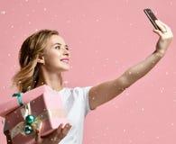 Молодые красивые подарки подарков на рождество владением женщины усмехаясь и сделать фото selfie с ее чернью мобильного телефона стоковые изображения