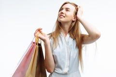 Молодые красивые покупки девушки, представляя с сумками подарка, на белом b Стоковые Изображения RF