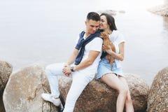 Молодые красивые положительные пары с небольшой собакой сидя на камне стоковое изображение rf