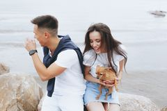 Молодые красивые положительные пары с небольшой собакой сидя на камне стоковое изображение