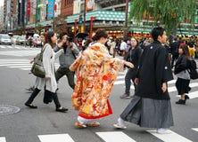 Молодые красивые японские пары одели в национальных японских костюмах и сфотографировали на токио города улицы, Японии стоковые изображения