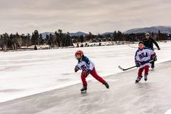 Молодые лыжники хоккея катаясь на коньках на озере зеркал стоковые фото