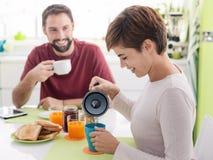 Молодые любящие пары имея завтрак дома стоковые изображения