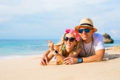 Молодые любящие пары лежа в песке на пляже Стоковое Изображение RF