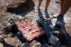 Молодые любящие пары на пикнике в горах Парень жарит мясо на коле в походе с его любимое Стоковые Фото