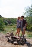 Молодые любящие пары на пикнике в горах Парень жарит мясо на коле в походе с его любимое Стоковые Фотографии RF