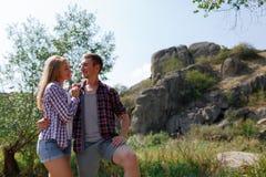 Молодые любящие пары на пикнике в горах Парень жарит мясо на коле в походе с его любимое Стоковая Фотография RF