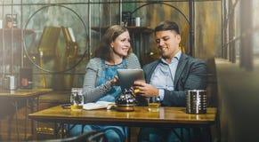 Молодые любящие пары сидя в кафе на таблице и используя планшет Девушка и парень используют цифровое устройство, blogging Стоковые Фотографии RF