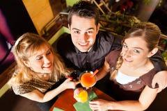 Молодые люди выпивая коктеилы в адвокатском сословии или ресторане стоковое фото