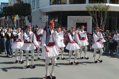 Молодые люди в национальных костюмах принимая участие в парад стоковые фото