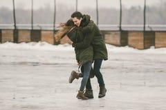 Молодые люди гетеросексуальные пары в студентах любов человек и кавказская женщина В зиме, в городской площади покрытой с льдом, стоковая фотография