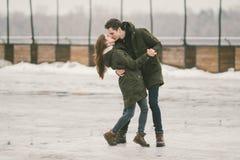 Молодые люди гетеросексуальные пары в студентах любов человек и кавказская женщина В зиме, в городской площади покрытой с льдом, стоковое изображение