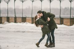 Молодые люди гетеросексуальные пары в студентах любов человек и кавказская женщина В зиме, в городской площади покрытой с льдом, стоковые изображения