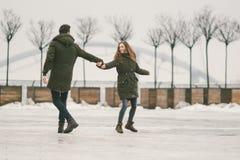 Молодые люди гетеросексуальные пары в студентах любов человек и кавказская женщина В зиме, в городской площади покрытой с льдом, стоковые фотографии rf