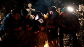 Молодые люди группы сидя в лесе зимы огнем Молодая женщина говоря ее друзьям страшный рассказ, держа сток-видео