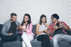 Молодые люди друзей смотря вниз на мобильном телефоне Сидеть на кресле и игнорировать каждые другие с на умными телефонами Стоковое фото RF