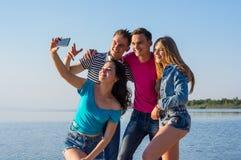 Молодые люди, друзья, смех и делает selfie на seashore Стоковая Фотография RF