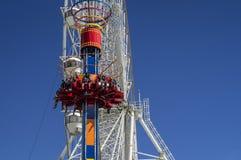 Молодые люди едет на башне падения в парке атракционов стоковые фотографии rf