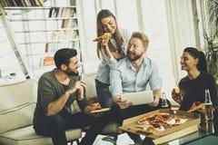 Молодые люди есть пиццу, выпивая сидр и наблюдая таблетку внутри Стоковые Изображения