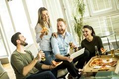 Молодые люди есть пиццу, выпивая сидр и наблюдая таблетку внутри Стоковое Изображение RF