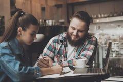 Молодые люди заполняют вне документы пока в кафе стоковое фото