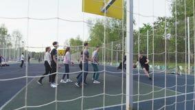 Молодые люди играет баскетбол на земле спорт среди парка акции видеоматериалы