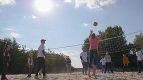 Молодые люди играет волейбол на песке в замедленном движении на небе и солнечном свете предпосылки сток-видео