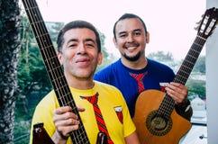 Молодые люди играя гитары с естественной предпосылкой стоковые изображения rf