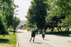 Молодые люди идя и свертывая в парке Muzeon с целью моста Krimsky, Москвы, России стоковые изображения rf