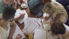 Молодые люди изучая в кафе видеоматериал