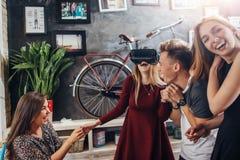 4 молодые люди имея новую технологию испытания партии стекел виртуальной реальности зрения 3d играя взаимодействующие игры стоковое фото