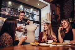 Молодые люди имея перерыв на чашку кофе ослабляя и обсуждая стоковые изображения