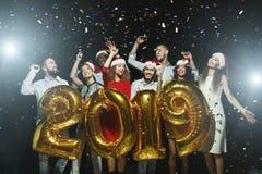 Молодые люди имея потеху на партии Нового Года стоковые изображения