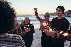 Молодые люди имея потеху с бенгальскими огнями на пляже стоковые фото