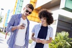 Молодые люди используя мобильный телефон на улице стоковое фото rf