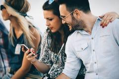 Молодые люди используя телефоны и беседовать стоковые фото