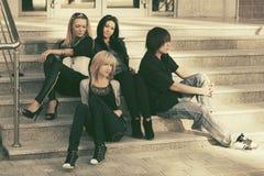Молодые люди и женщины битника моды сидя на шагах Стоковое Изображение