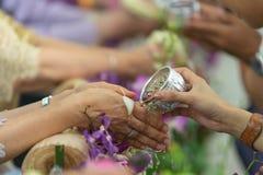 Молодые люди лить воду и цветки на руках старшия в церемонии Songkran Стоковые Фотографии RF