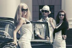 Молодые люди моды рядом с винтажным автомобилем в улице города Стоковая Фотография