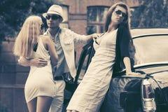 Молодые люди моды рядом с ретро автомобилем в улице города Стоковая Фотография RF