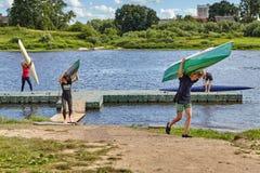 Молодые люди носит каяки на плечах после тренировки на rowing Стоковые Фотографии RF