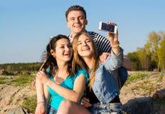 Молодые люди - парень и 2 девушки - смех и делает selfie в Стоковые Изображения RF
