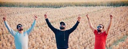 3 молодые люди поднимая руки стоя в месте стоковое изображение
