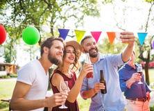 Молодые люди принимая selfie на партию снаружи в задворк стоковые фото