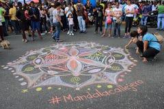 Молодые люди рисуя мандалу для любов и мира в улицах Каракаса во время светомаскировки Венесуэлы стоковое фото rf